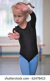 closeup of little gymnast girl doing exercises