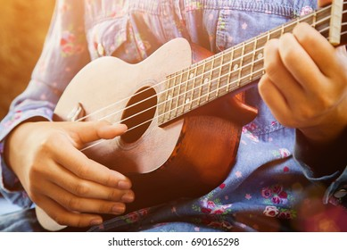 Close-up of little hipster girl playing ukulele guitar, vintage film tone effect