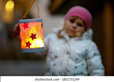 Close-up of little kid girl holding selfmade lanterns with candle for St. Martin procession. Healthy toddler child happy about children and family parade in kindergarten. German tradition Martinsumzug