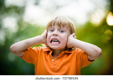Close-up of a little kid in an orange t-shirt holding his hands to his ears and screaming loudly