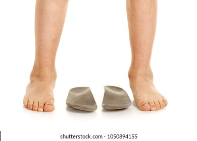 Closeup of little male barefoot legs and orthopedic insoles for shoes
