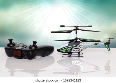 Closeup of a little RC toy helicopter and a remote controller on a bright table against abstract blue sunrays background. Macro photograph.