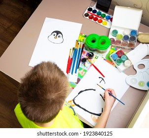 Closeup of little toddler boy drawing picture with colorful paint using brush. Child education at home during self isolation and lockdown. Concept of art and creativity of children.