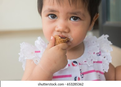 Closeup little toddler girl with an ice cream cone in hand, asian girl and ice cream