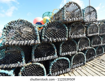 Closeup of lobster and crab creels piled up in a row with red and yellow bouys on top, in the harbour of the fishing village of Anstruther, Kingdom of Fife near St. Andrews, Scotland.