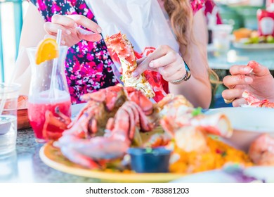 Closeup of lobsters and seafood on plate with woman shucking or shelling crab leg with hands on platter