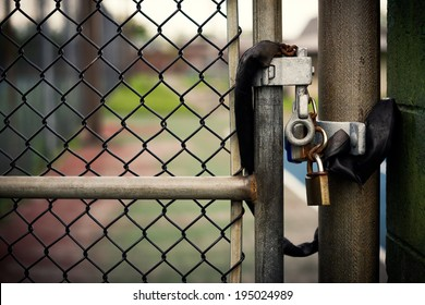 Closeup of a locked padlock securing a metal chain-link gate.