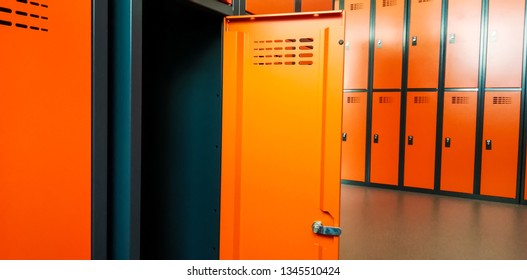 Closeup of locker room situated in work place. Orange lockers, storage for workers.