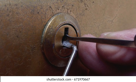 Close-up Of Lockpicker Hand Opening locker