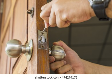 close-up locksmith repair silver lock on wood door -