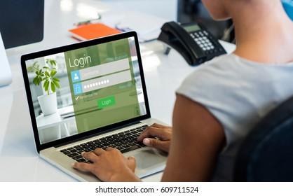 Close-up of login page against woman working on laptop while sitting on chair