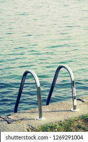 Closeup of a lonely swimming pool in the outdoorsoutdoors, with a metallic ladder leading to the clear water