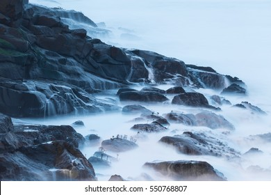 Closeup long exposure of seawater running off of eroded lava rocks creates an other-worldly landscape