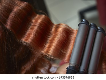 Closeup of long red hair curled with electric triple barrel curling iron in a hairdressing salon.