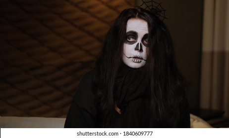 Close-up of a long-haired girl in a black cloak as a cute zombie, who sits on the bed, sighs deeply and pretends to be offended at everyone. Halloween Eve. October holiday.