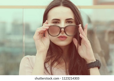 Close-up: long-haired young brunette woman posing while playing with sunglasses. Fashionable style with pink tones. Blurred background. The wind plays with brunette hair.