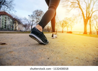Closeup look of the shoes of a jogging women in a park