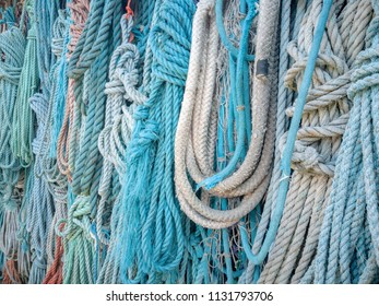 Closeup of lots of old, blue and frayed nautical rope.
