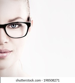 Close-up of lovely woman in optical eyeglasses. Young beautiful Caucasian female model wearing specs posing in studio.