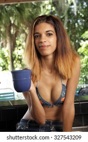 A closeup of a lovely young Hispanic girl with a friendly smile, holding a cup of coffee.