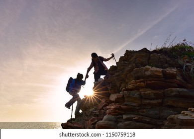 Close-up of loving couple hikers climbing up on the peak of mountain. Climbing ,Helps and Team work concept .