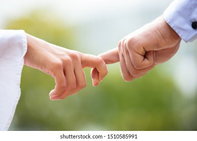 Close-up Of Loving Couple Holding Each Other's Finger Against Blurred Background