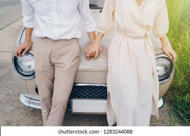 Closeup of loving couple holding hands on road trip at sunset. Love, Valentine and wedding concept.