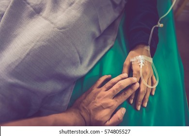 Closeup of loving couple holding hands while sick , Hand of man touching woman in clinic , holding hands retro background, closeup