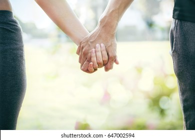 Closeup of loving couple holding hands while walking at sunset with flare