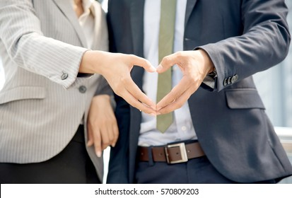 Closeup of loving couple  standing side by side at the terrace. Happy Young businessman making a heart shape with his girlfriend. Valentines Day, loving concept.