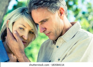 Closeup of loving man comforting woman in a park