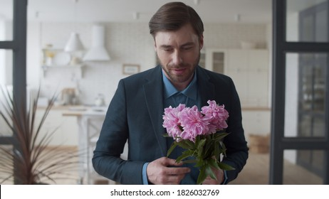 Closeup loving man presenting bouquet of flowers to wife at home in slow motion. Loving family relaxing on couch at home. Handsome man hugging woman with flowers on couch in living room.