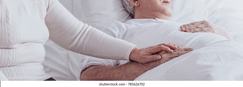 Close-up of loving senior woman supporting her sick husband at hospital, holding his hand