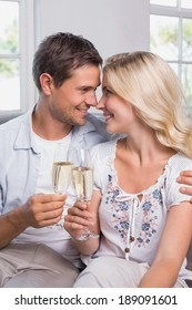 Close-up of a loving young couple with champagne flutes at home