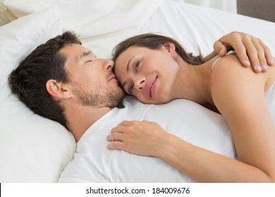 Close-up of a loving young couple lying in bed at home