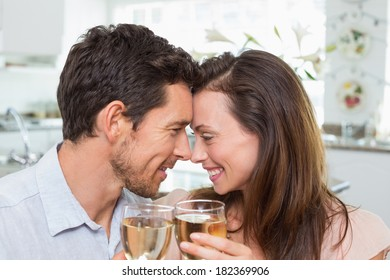Close-up of a loving young couple with wine glasses at home