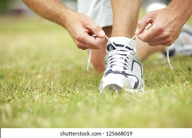Closeup low angle view across grass of a young man's hands tying the laces on his trainers.