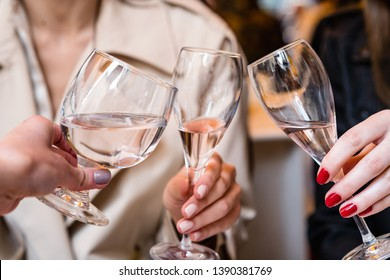 Closeup low angle view of group of unrecognizable people toasting with wine. Friend toasting saying cheers