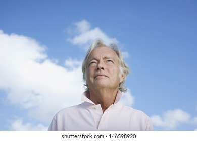 Closeup low angle view of a mature man against the sky