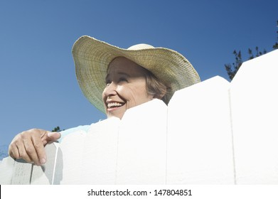 Closeup low angle view of a smiling woman peering over garden fence