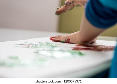 Closeup low angle view of toddler child making colourfull palm prints with finger paints on a piece of white paper.