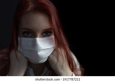 Closeup low key portrait of beautiful redhead young woman with medical face mask on the black background.