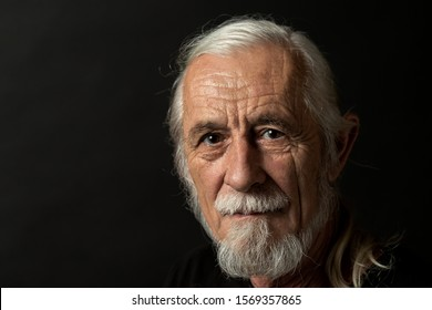 Closeup low key studio portrait of beautiful gray hair old man looking at the camera. Horizontally.