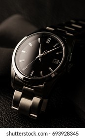 closeup luxury automatic wristwatch for men with black dial and stainless steel bracelet.