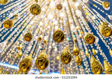 Closeup of a luxury crystal chandelier details . Light bokeh pattern background.