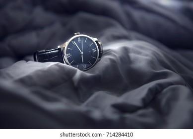 Closeup luxury man wrist watch black dial on gray fabric background. Dark toned.
