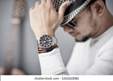closeup luxury men watch with black dial and stainless steel bracelet on wrist of man.