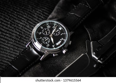 Closeup at luxury men wristwatch with black dial and leather strap.