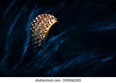 Gros plan sur une alliance de luxe sur fond bleu clair. Un cadeau de bijoux en or avec des pierres précieuses. Les bijoux anciens élégants sont encore en vie. Bijoux.