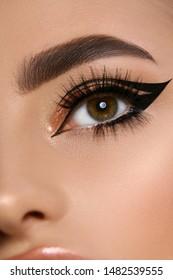 Nahaufnahme eines luxuriösen Frauenauges mit schwarzem Wimperntuscher, perfekter Schminkgeschmack, weibliche offene Augen mit dunkelgoldfarbenem Mua